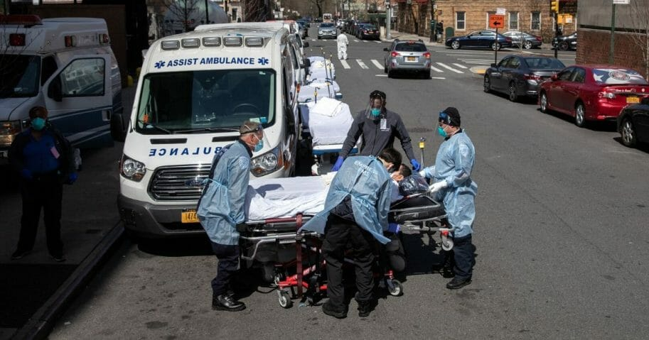 Medics and hospital workers prepare to lift a COVID-19 patient onto a hospital stretcher outside the Montefiore Medical Center Moses Campus on April 7, 2020, in the Bronx borough of New York City.