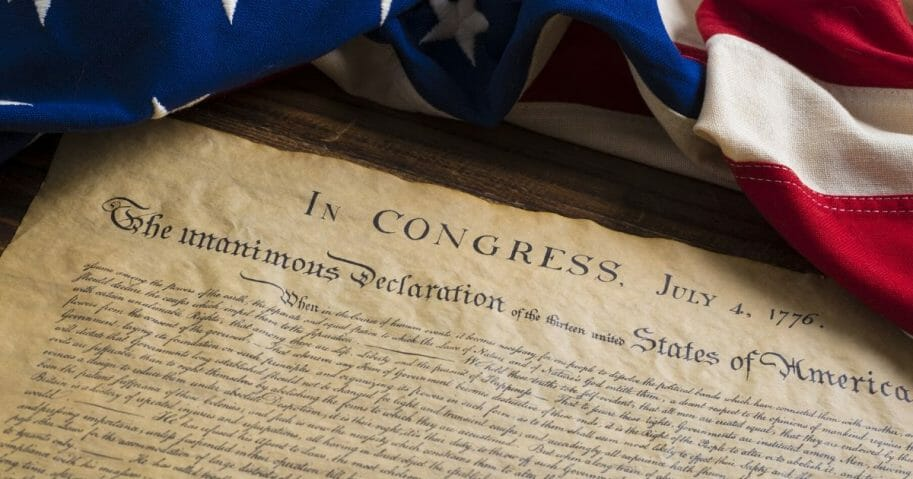 Stock image of the Declaration of Independence sitting on a vintage flag.