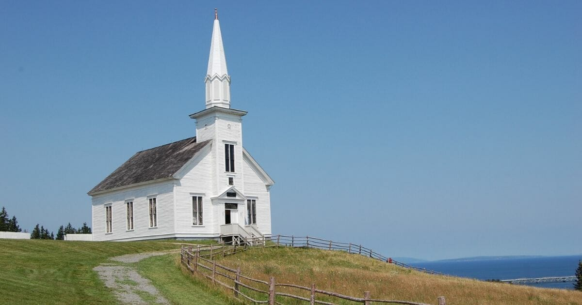 Stock image of a country church in Nova Scotia, Canada, overlooking the sea.