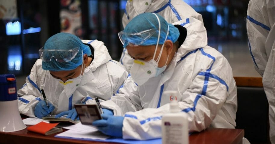 Chinese security officers garbed in hazmat suits check internal passports at the Wuhan train station in Wuhan, China.