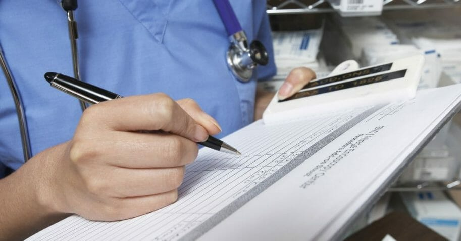 Stock image of a medical professional holding a patient's chart.