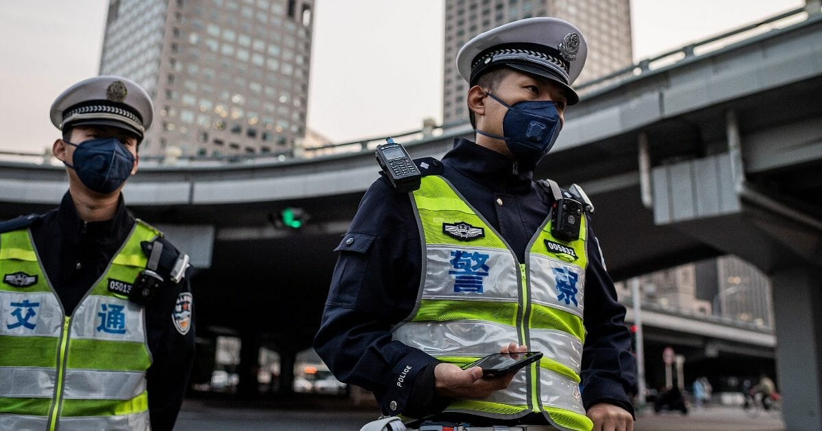 Police officers wearing face masks stand at a street crossing in Beijing on April 7, 2020.