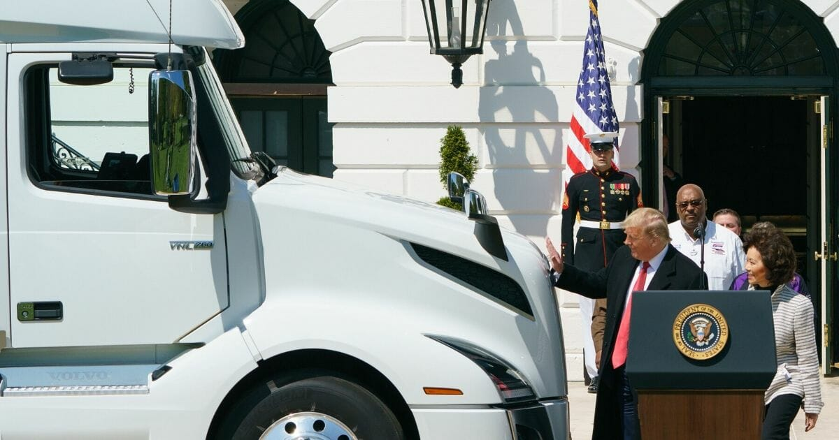 President Donald Trump reaches out to pat the hood of a truck outside the White House on Thursday as he and Transportation Secretary Elaine Chao arrive for an event to celebrate Americantruckers and their role in supplying the country during the coronavirus crisis.