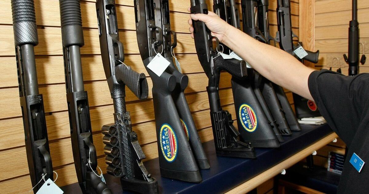 A hand reaches for a rifle on a gun store rack.