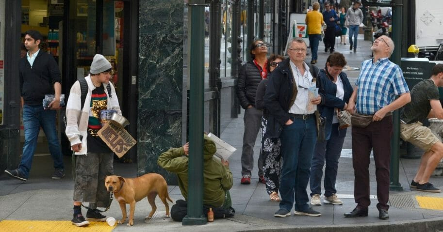 A man with a dog and a sign asking for money stands at a street corner in San Francisco.