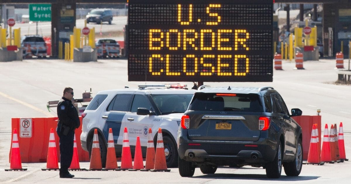 Customs officers speak with people in a car beside a sign saying that the U.S. border is closed at the U.S.-Canada border in Lansdowne, Ontario, on March 22, 2020.