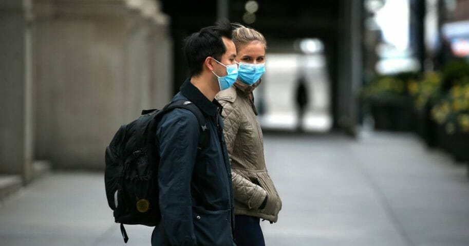 Two people wearing protective masks on a walk during the coronavirus pandemic on April 18, 2020, in New York City.