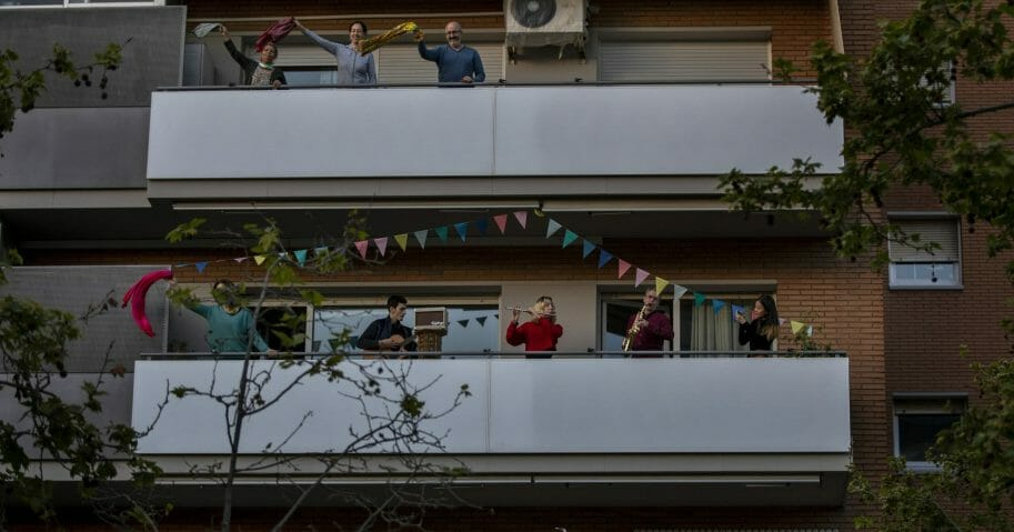 People play instruments as others dance on their balconies in support of the medical staff that are working on the COVID-19 virus outbreak in Barcelona, Spain, on April 5, 2020.