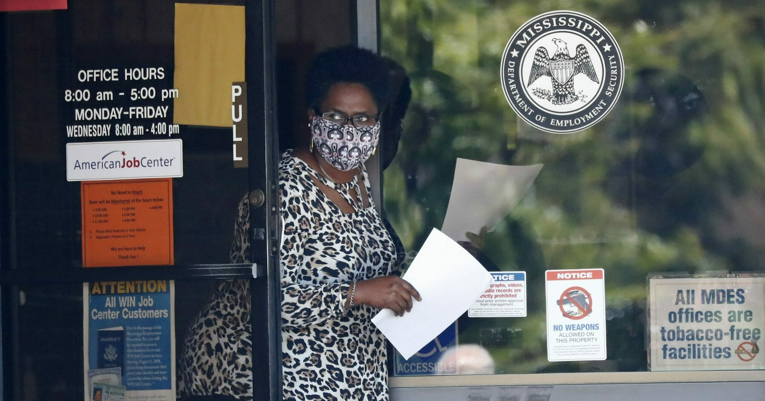 A masked worker at the state WIN Job Center in Pearl, Mississippi, holds an unemployment benefit application form as she waits for a client April 21, 2020