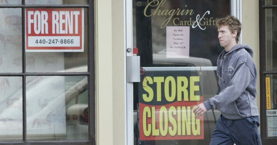 A man walks past a closed business in Chagrin Falls, Ohio, on April 29, 2020.