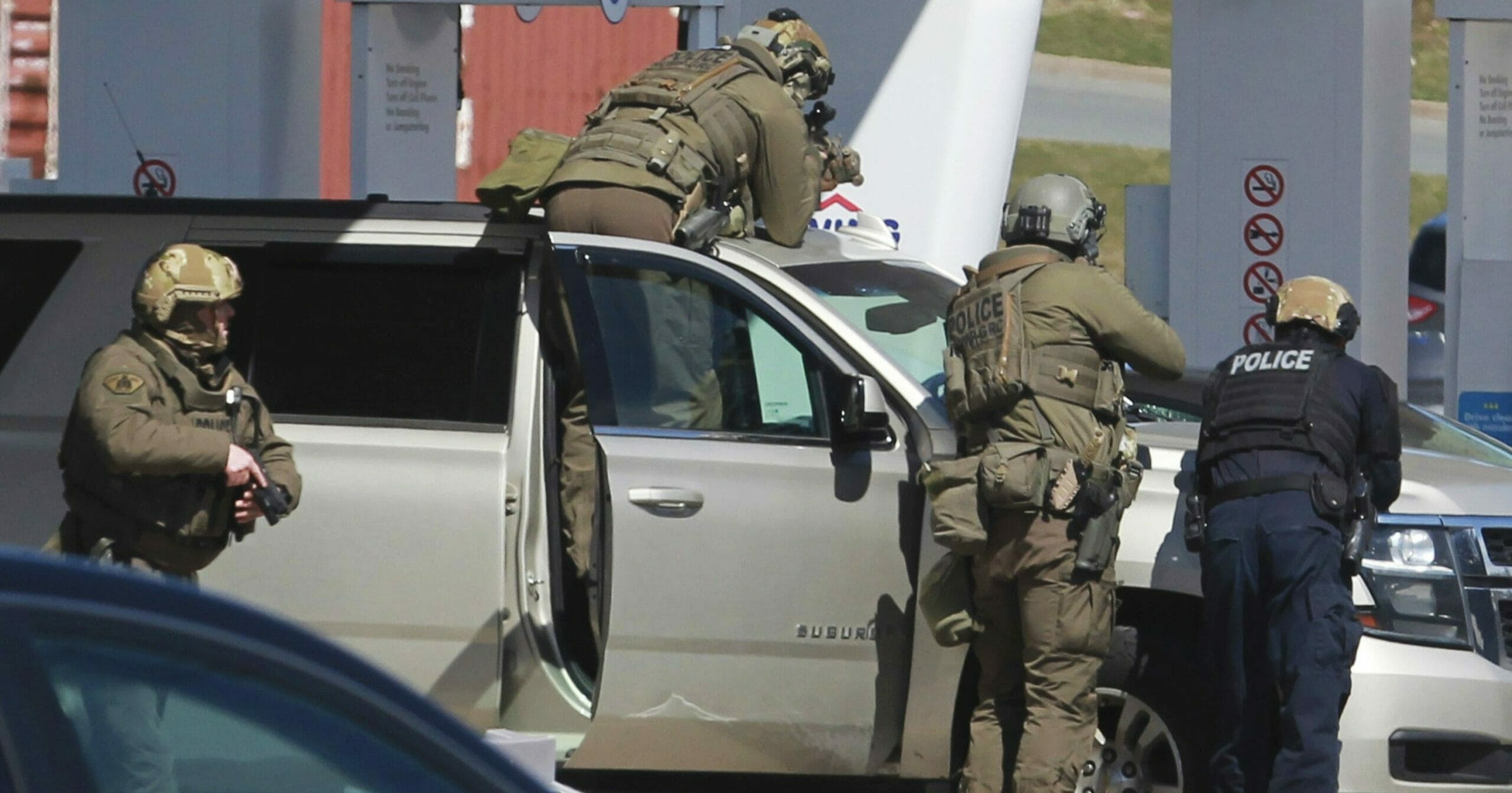 Royal Canadian Mounted Police officers surround a suspect at a gas station in Enfield, Nova Scotia, on April 19, 2020.