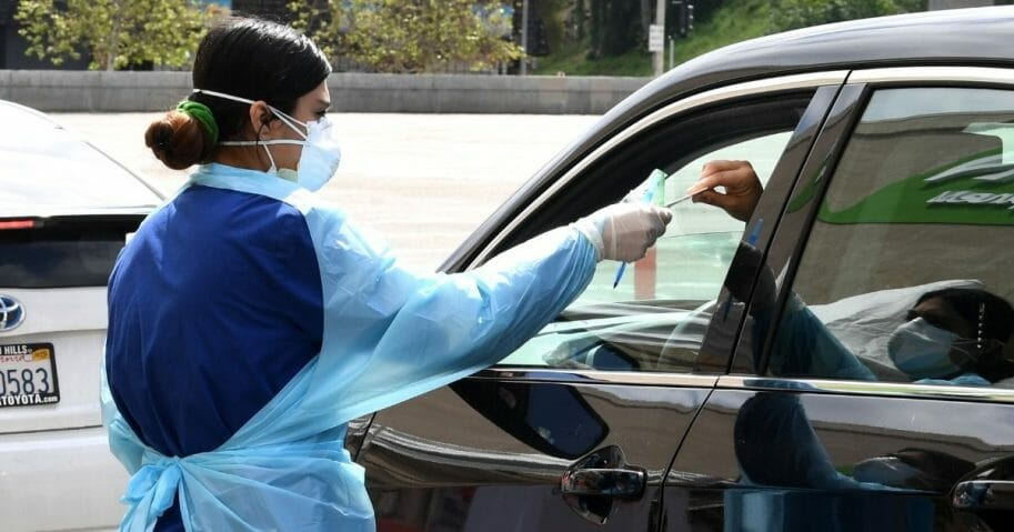 A worker wearing personal protective equipment gathers the tests administered from a car as Mend Urgent Care conducts drive-thru testing for COVID-19 at the Westfield Fashion Square on April 13, 2020, in the Sherman Oaks neighborhood of Los Angeles, California.