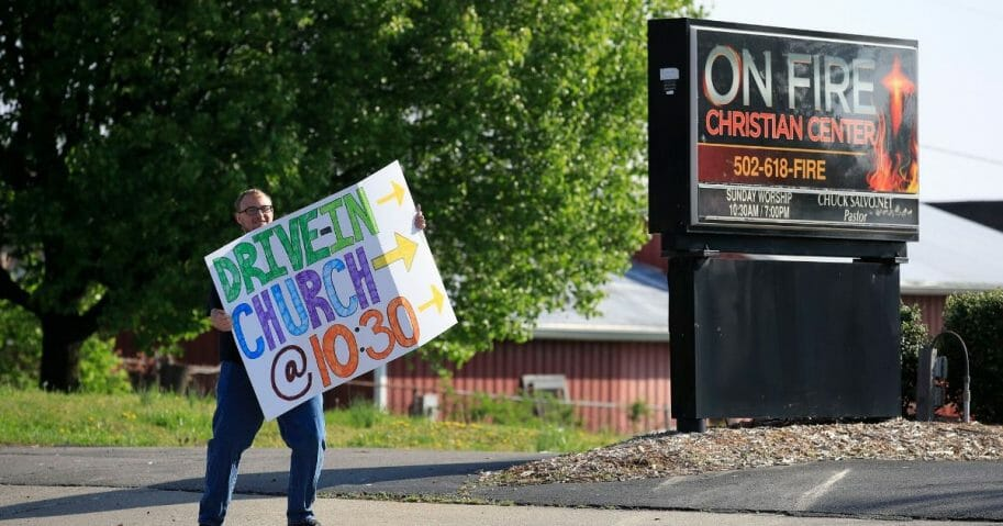 A worshiper holds a sign to alert drivers to a drive-in service