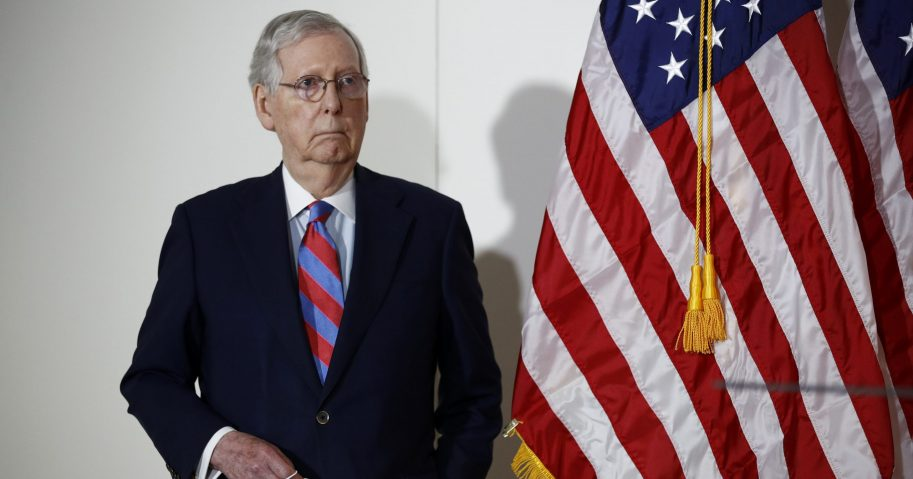 Senate Majority Leader Mitch McConnell of Kentucky holds a face mask used to protect against the spread of the new coronavirus as he attends a news conference on Capitol Hill in Washington on May 12, 2020.
