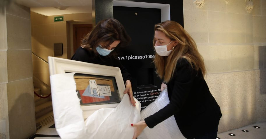 "Raffle organizers Peri Cochin, left, and Arabenne Reille unbox the painting ""Nature morte"" by Picasso at Christie's auction house on May 19, 2020, in Paris."