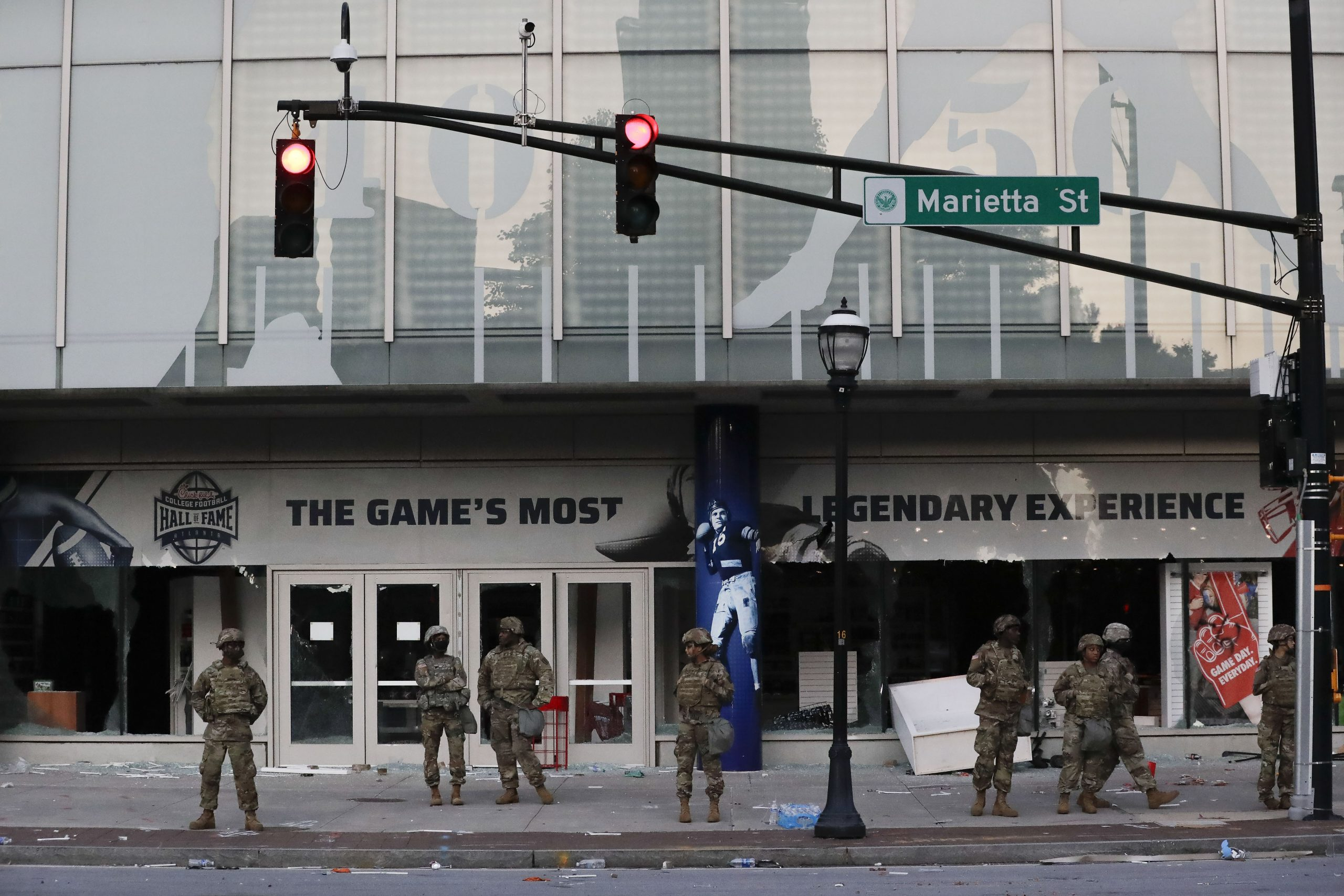 Members of the Georgia National Guard line up in front of the of the College Football Hall of Fame on Saturday in the aftermath of a riot Friday that started as a demonstration against police violence.