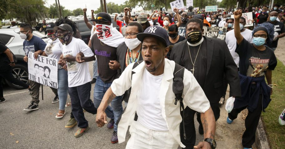 Malik Muhammad, center, joins a group of people marching from the Glynn County Courthouse in downtown to a police station after a rally to protest the shooting of Ahmaud Arbery on May 16, 2020, in Brunswick, Georgia.