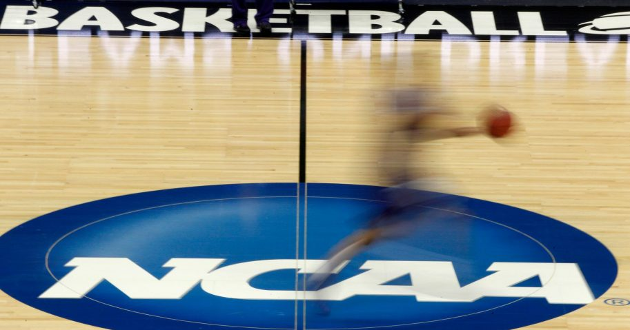 A player runs across the NCAA logo during practice in Pittsburgh before an NCAA tournament college basketball game.