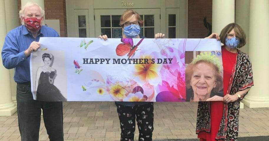 This May 3, 2020, photo released by Shelly Solomon shows, from left, Steve Turner and his sisters, Carla Paull and Lisa Fishman, holding up a Mother's Day banner emblazoned with images of their mom, Beverly Turner, in front of her assisted living facility in Ladue, Missouri.