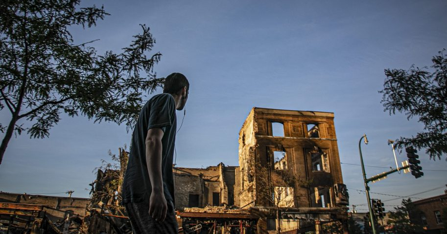 A man walks on Lake Street while looking at businesses destroyed during riots over the death of George Floyd on Sunday May 31, 2020, in Minneapolis. Floyd died after being restrained by Minneapolis police officers on May 25.