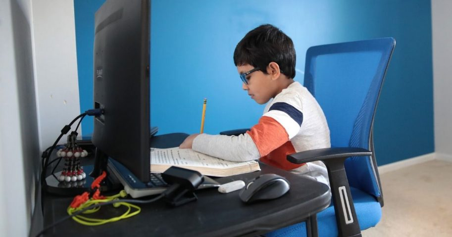 Seven-year-old Hamza Haqqani, a second-grader at Al-Huda Academy in Illinois, uses a computer to participate in an E-learning class with his teacher and classmates from his home in Bartlett on May 1, 2020.