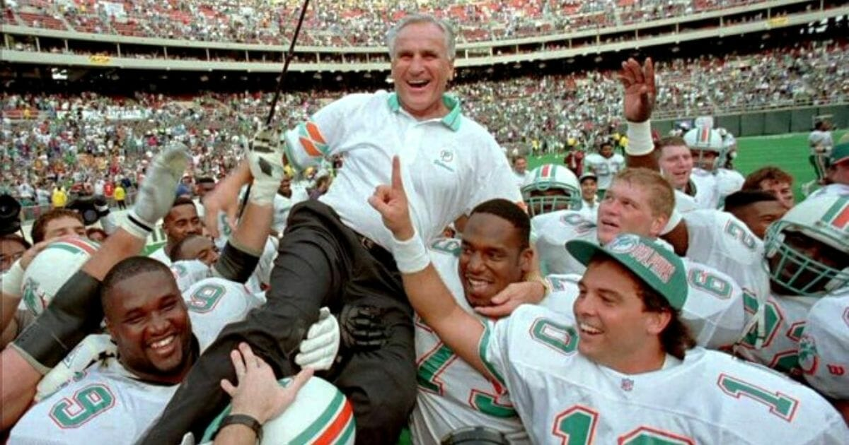 Miami Dolphins coach Don Shula is carried off the field by his players.