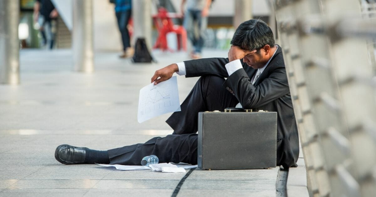 A businessman who has been fired sits down on the street in the stock image above.