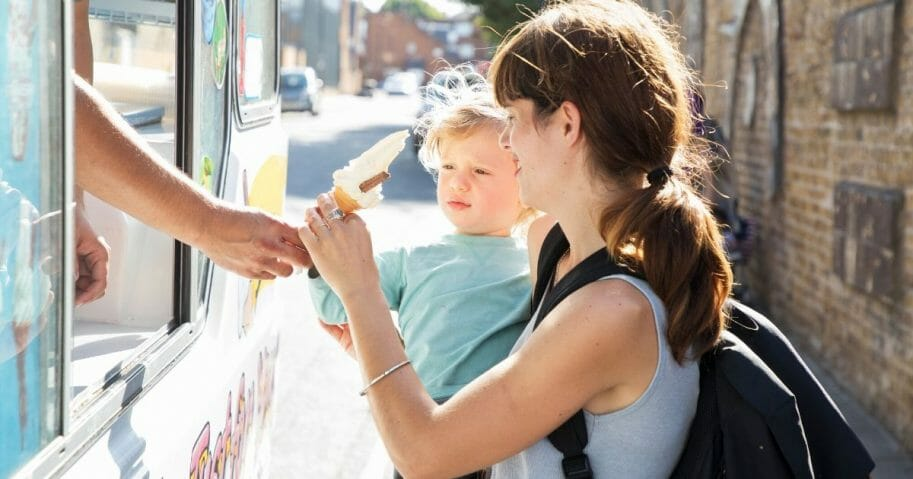 An ice cream seller gives ice cream to a mother and her toddler in the stock image above.