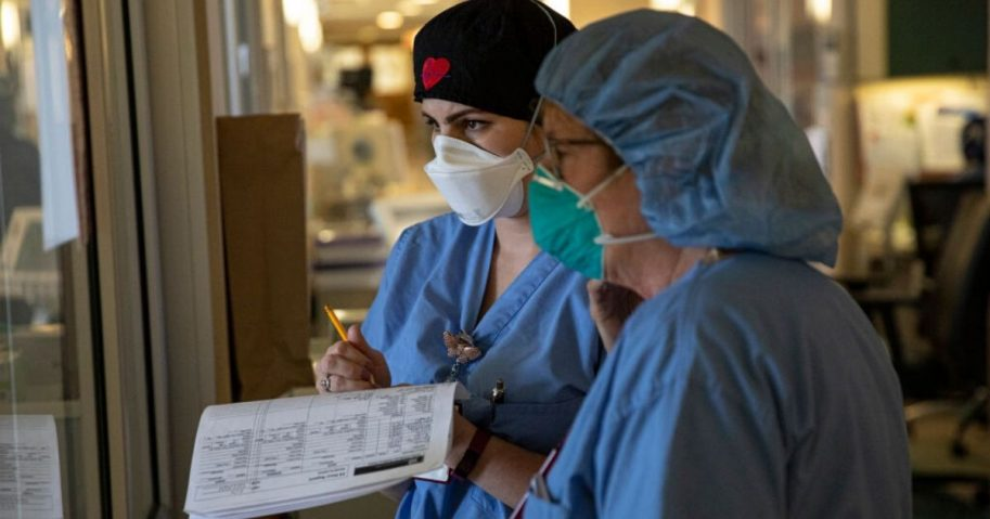 Two nurses assess the vital signs of a COVID-19 patient on the intensive care unit floor at the Veterans Affairs Medical Center on April 21, 2020, in the Brooklyn borough of New York City.