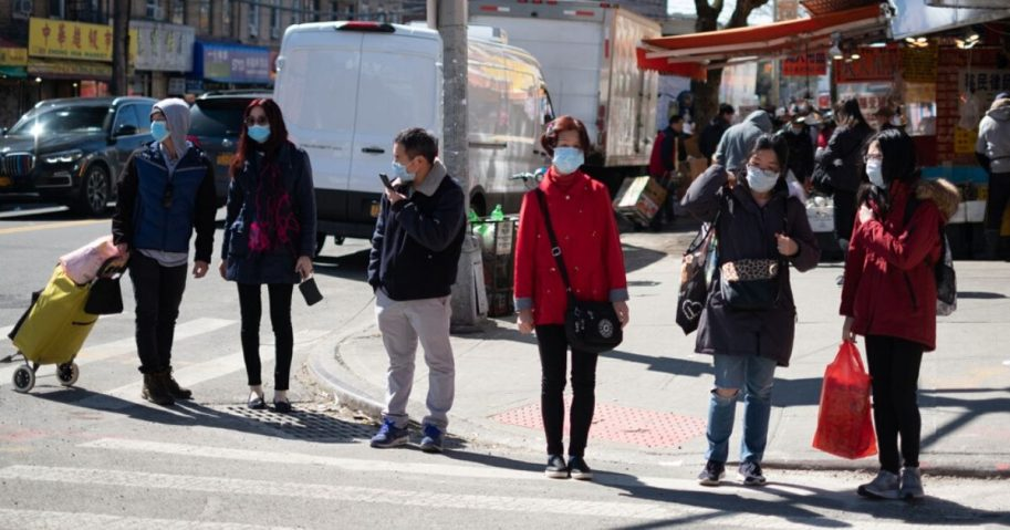 People wear masks on a New York City street in the stock image above.