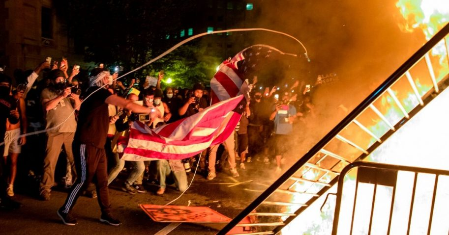 Rioters throw an American flag into a fire during a demonstration outside the White House on May 31, 2020.