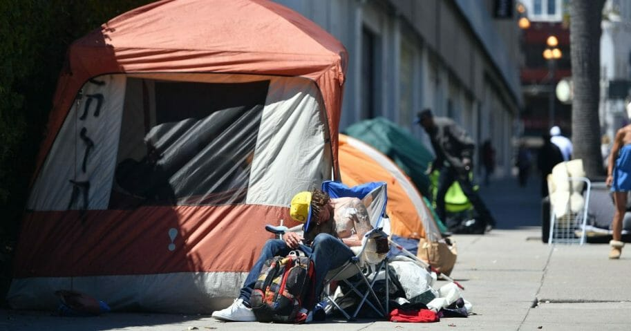 A homeless man sleeps in front of his tent along Van Ness Avenue in downtown San Francisco, California, on June, 27, 2016.