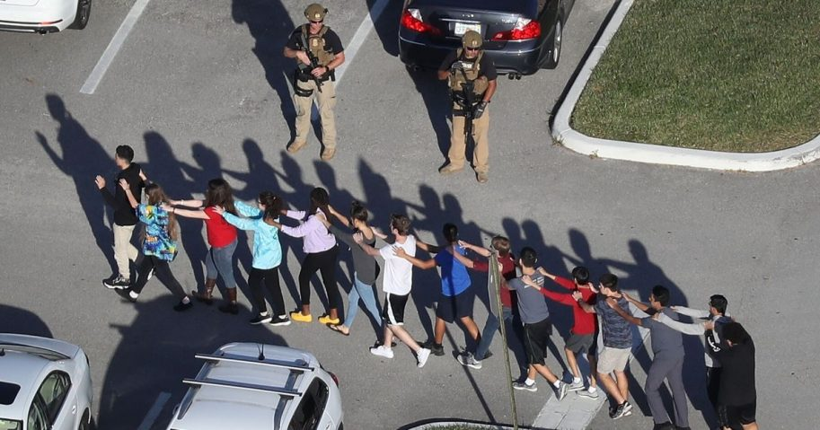 People are brought out of Marjory Stoneman Douglas High School after a shooting at the school on Feb. 14, 2018, in Parkland, Florida.