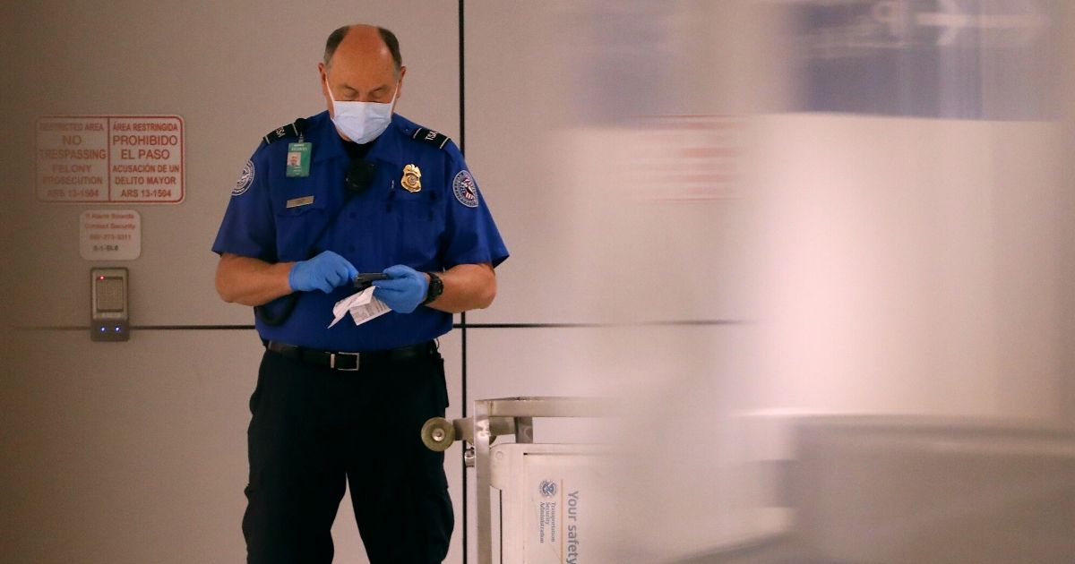 A TSA agent looks at his cellphone while wearing a mask and gloves at Sky Harbor Airport on March 12, 2020, in Phoenix, Arizona.