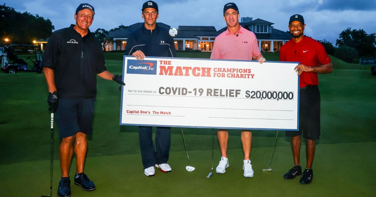Phil Mickelson, Tom Brady, Peyton Manning and Tiger Woods display a check showing their event raised $20 million for COVID-19 relief.