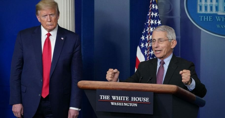 Dr. Anthony Fauci, director of the National Institute of Allergy and Infectious Diseases, is flanked by President Donald Trump as he speaks during the daily briefing on the coronavirus at the White House on April 22, 2020.