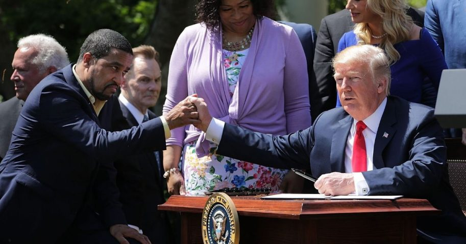 President Donald Trump shakes hands with Pastor Darrell Scott, co-founder of the New Sirit Revival Center, before Trump signs an executive order during an event in the Rose Garden to mark the National Day of Prayer at the White House May 3, 2018, in Washington, D.C.
