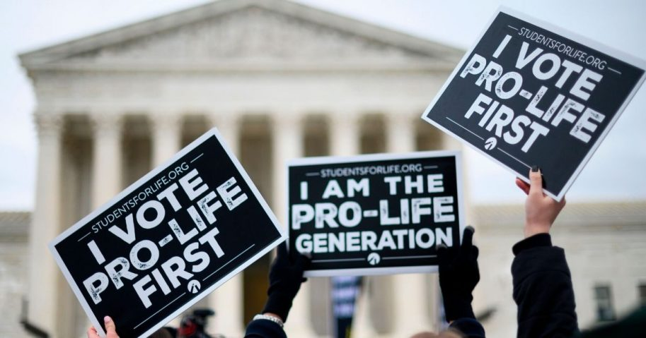 Pro-life advocates hold signs as they stand in front of the Supreme Court while participating in the 47th annual March For Life in Washington, D.C., on Jan. 24, 2020.