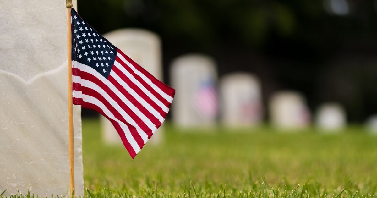 Stock image of small American flags and headstones at a cemetery.