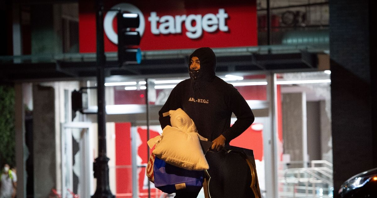 A looter robs a Target store as riotsarose in Oakland, California, on Saturday.