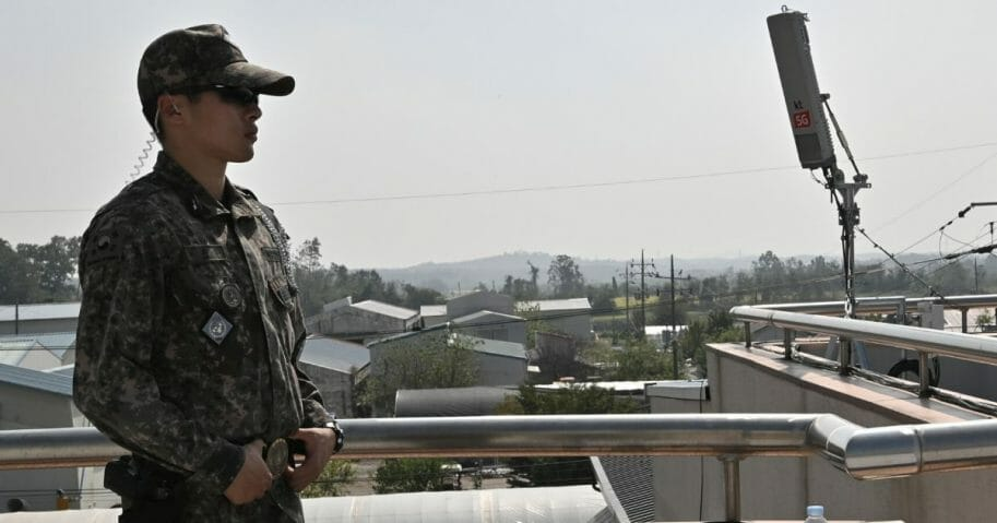 A South Korean soldier stands guard next to an antenna for the 5G mobile network service on the rooftop of a building during a media tour to the Taesungdong freedom village in the Demilitarized Zone dividing the two Koreas in Paju on Sept. 30, 2019.