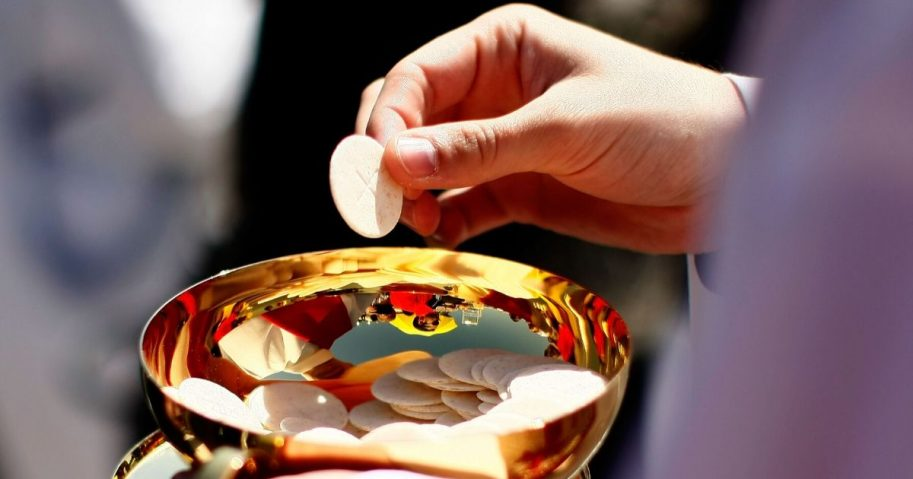 A priest holds a Holy Communion wafer as Pope Benedict XVI celebrates Mass at Nationals Park in Washington on April 17, 2008.