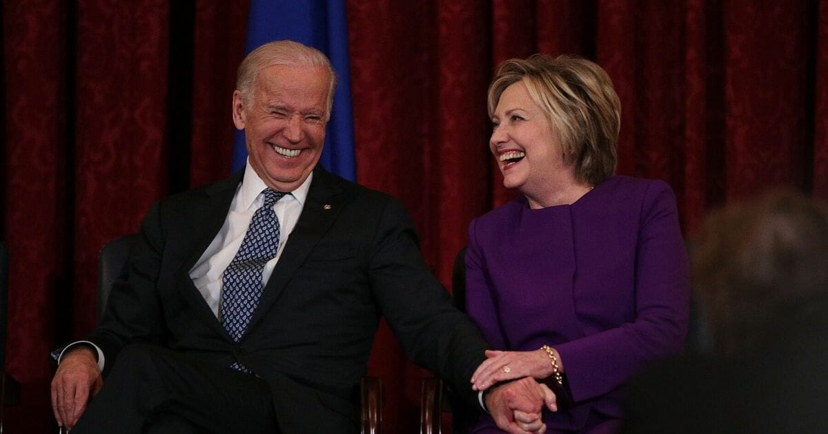 Former Secretary of State Hillary Clinton laughs with then-Vice President Joseph Biden during a leadership portrait unveiling ceremony for former Senate Minority Leader Sen. Harry Reid on Dec. 8, 2016, on Capitol Hill in Washington, D.C.