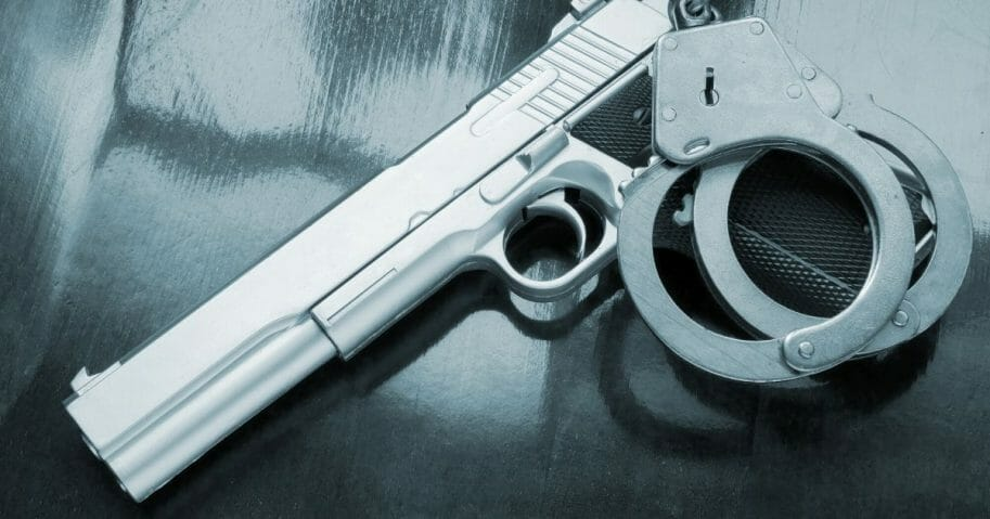 Stock image of a handgun and handcuffs on a table.