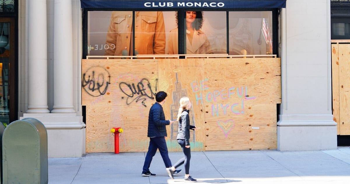 People walk by a boarded-up storefront during the coronavirus pandemic on April 19, 2020, in New York City.