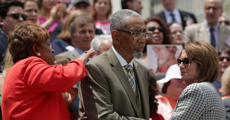 Democratic Rep. Bobby Rush of Illinois, center, is comforted by then-House Minority Leader Nancy Pelosi and Democratic Rep. Brenda Lawrence of Michigan, left, after he spoke during a news conference on gun control on June 22, 2016, on Capitol Hill in Washington, D.C.