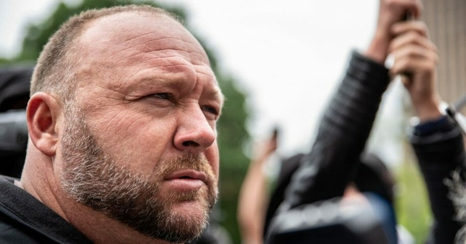 Conspiracy theorist and Infowars founder Alex Jones listens to a supporter at the Texas state Capitol on April 18, 2020, in Austin, Texas.