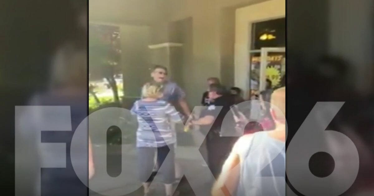 A man is handcuffed by police in Fresno, California, for attempting to patronize a restaurant that had opened its dining room despite a lockdown order.