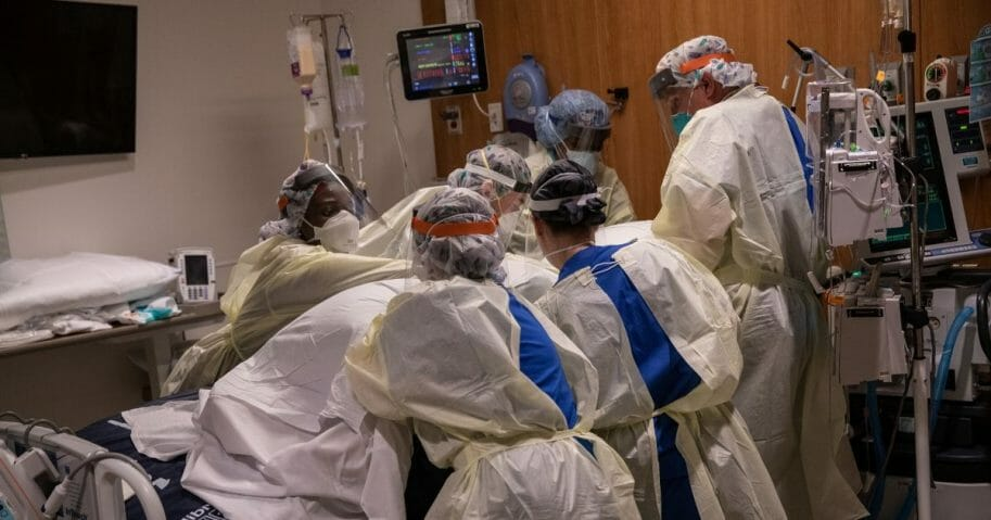 """A """"prone team,"""" wearing personal protective equipment, turns a COVID-19 patient onto his stomach in a Stamford Hospital intensive care unit on April 24, 2020, in Stamford, Connecticut."""
