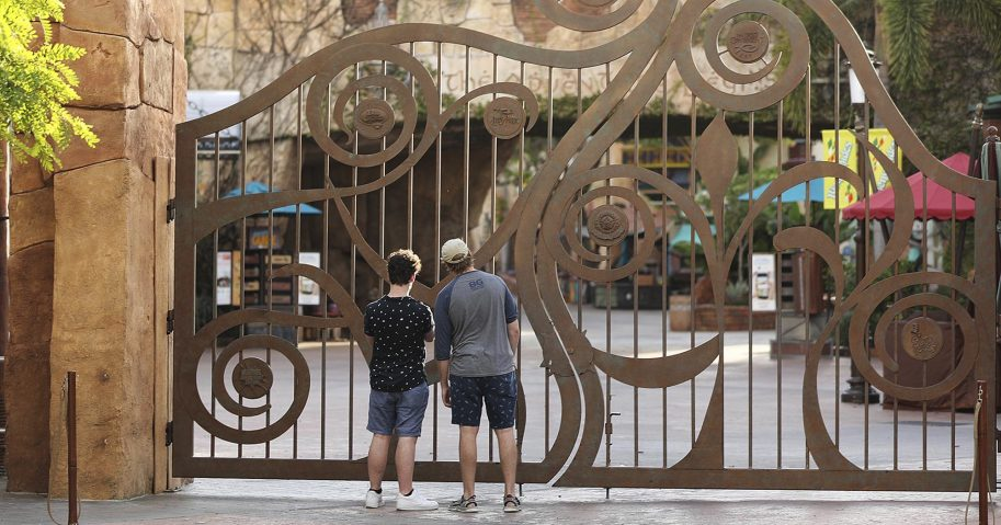 In this May 14, 2020, file photo, guests peer through the closed gate to Universal's Islands of Adventure beside Universal CityWalk, in Orlando, Florida.